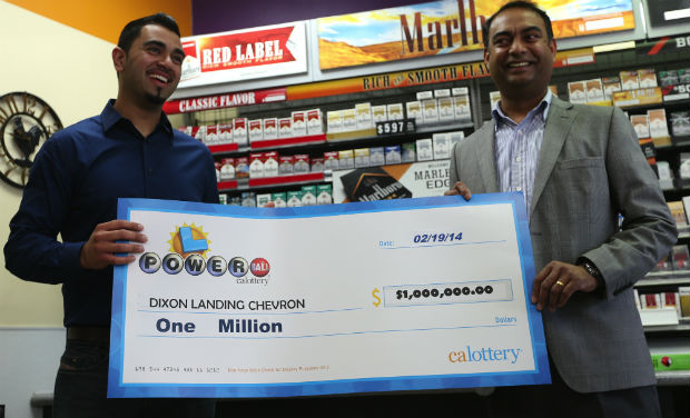 Parmeet Singh, son of Dixon Landing Chevron store owner Kulwinder Singh, left, and his uncle Karam Singh, vice president of operations, are presented with an oversized check for $1 million at the store in Milpitas, California, on Thursday - AP